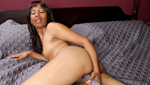 Skinny ethnic milf Robin uses her purple dildo to please her moist mature pussy.