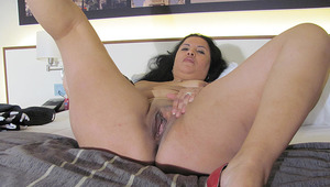 dirty older girl playing on her bed with a dildo